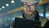 Engineer in hardhat is using a tablet computer in a heavy industry factory.