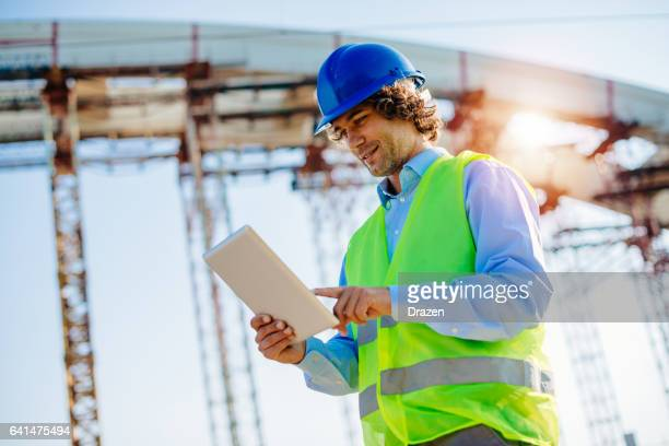 Engineer in protective clothing on construction site with digital blueprints