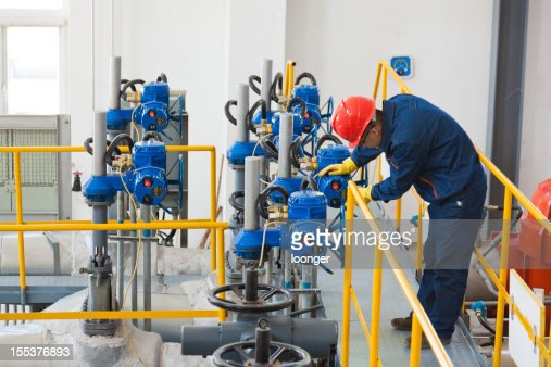 Engineer in protective wear checking oil pipes equipment