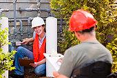 Engineer in wheelchair discussing energy efficiency data with female engineer in front of gas meter