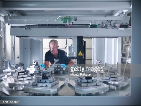 Engineer inspecting automatic lathe in factory