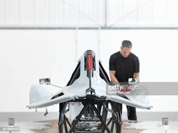 Engineer inspecting carbon fibre car body shell in sports car factory