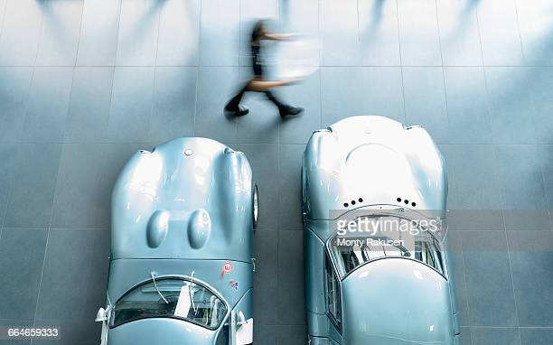 Engineer inspecting classic racing cars in racing car factory, overhead view