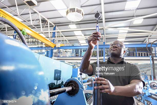 Engineer inspecting component in engineering factory