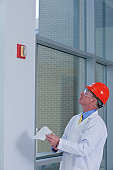 Engineer inspecting fire alarm in a building