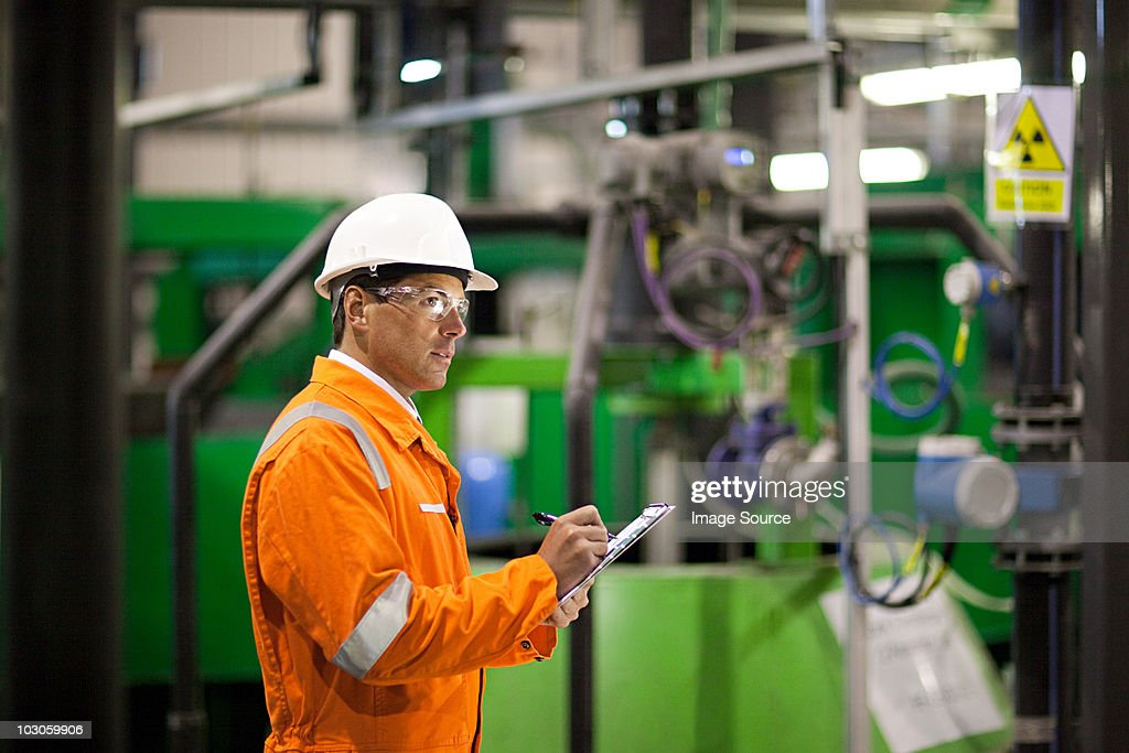 Engineer inspecting machinery in factory : Stock Photo