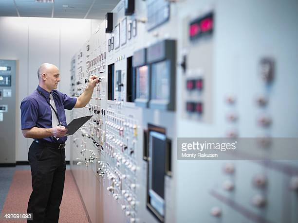 Engineer inspecting nuclear power station control room simulator
