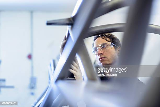Engineer inspecting racing car roll cage in racing car factory