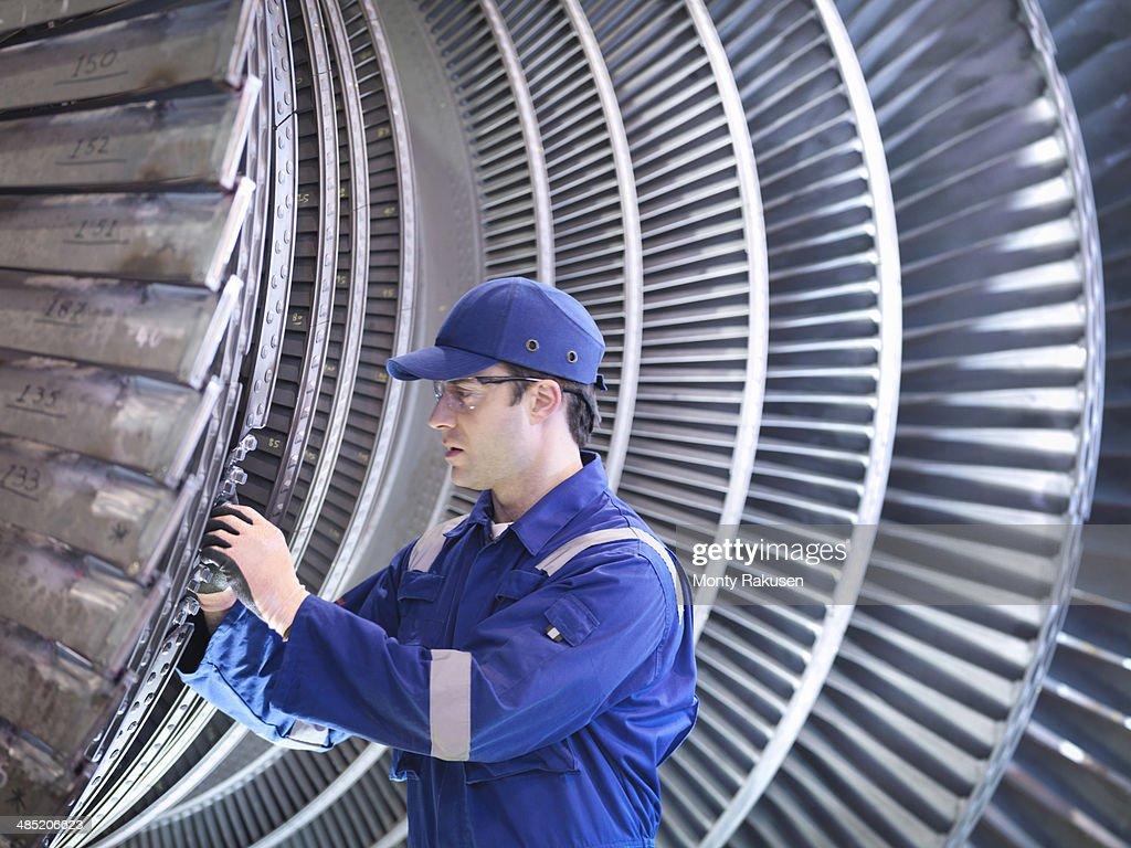 Engineer inspecting repair to steam turbine blade in workshop