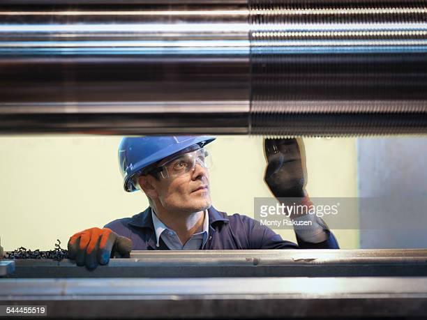 Engineer inspecting turned steel in engineering factory
