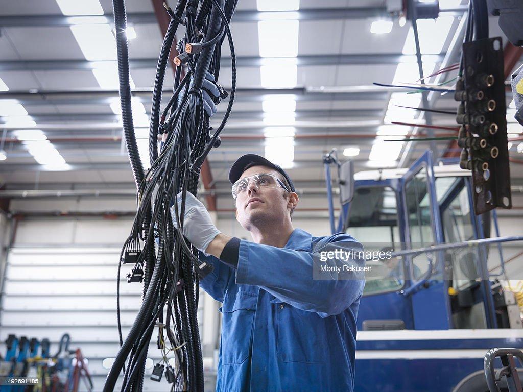 Engineer installing new electrics in truck repair factory