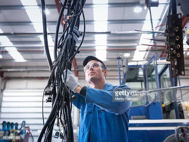 Engineer installing new electrics in truck repair factory