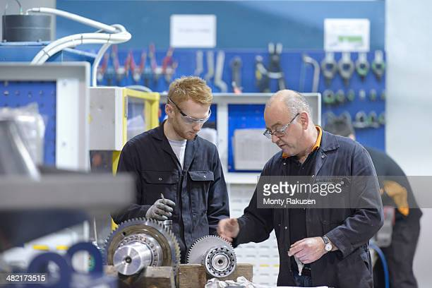 Engineer instructing apprentice at workstation in factory