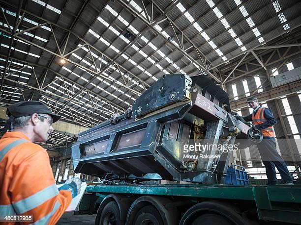 Engineer loading steel part onto truck in factory