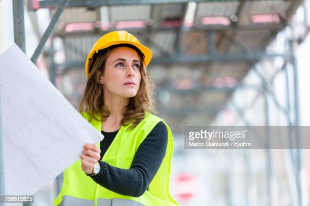 Engineer Looking Away While Holding Blueprints