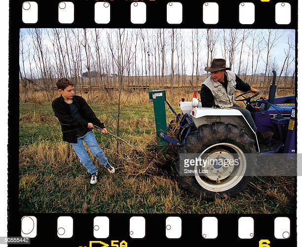 Engineer Louis Licht riding tractor while son Rustin works behind him re Licht's discovery that popular trees when planted near streams or rivers can...
