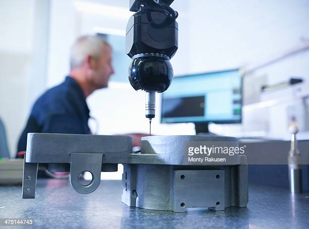 Engineer measuring components in factory