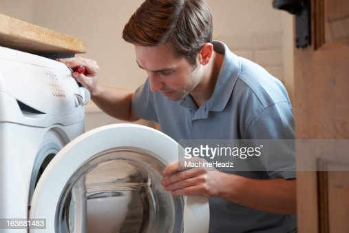 Engineer Mending Domestic Washing Machine Stock Photo | Getty Images: http://gettyimages.com/detail/photo/engineer-mending-domestic-washing-machine-royalty-free-image/163881483