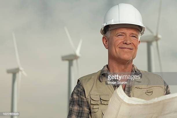 Engineer on a wind farm with plans