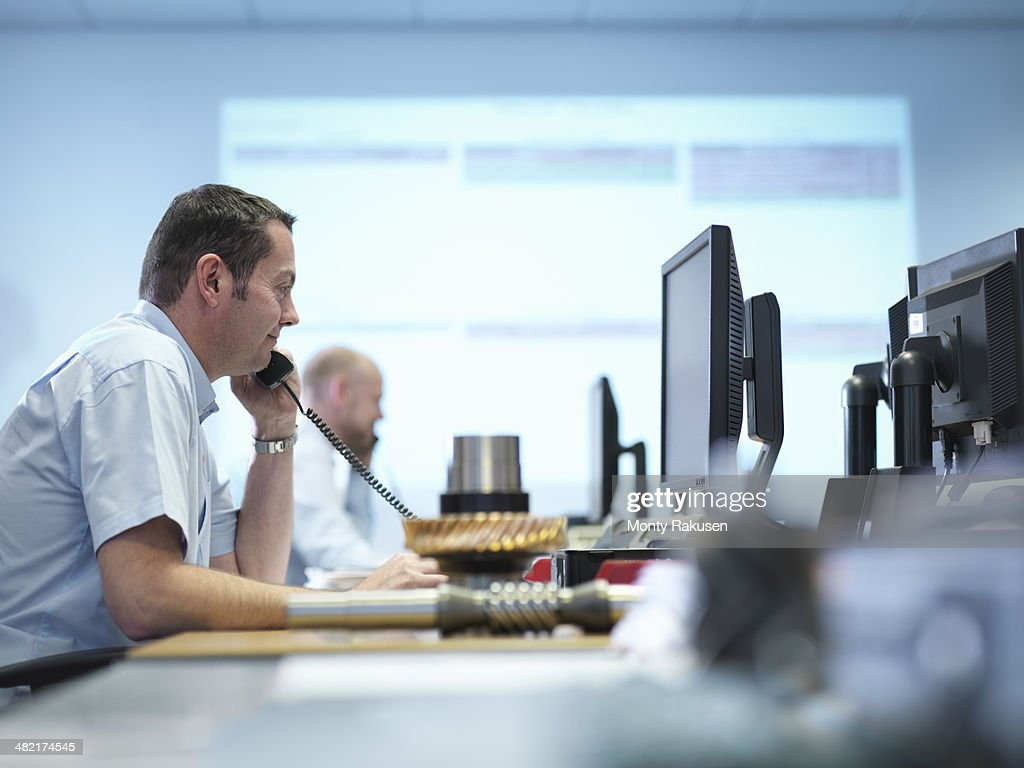 Engineer on the phone and using computer aided design in factory office