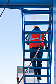 Engineer on upper staircase of industrial plant