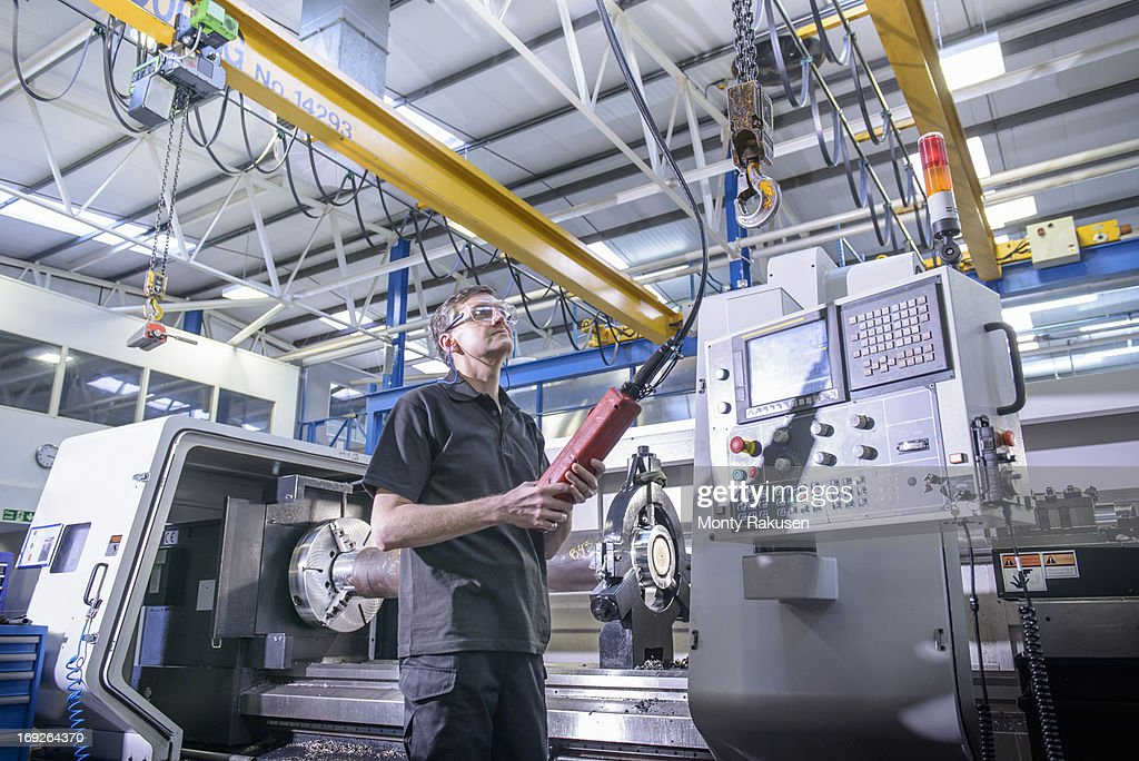 Engineer operating crane in front of industrial lathe in factory