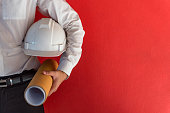 Engineer or Architect holding personal protective equipment safety helmet and architectural drawing in red background. Engineering, Architecture and building construction management concepts