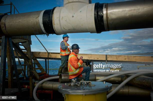 Engineer Philip Kennedy and Jack Huffman are working on the barge that they are filling with Iceberg ice As more icebergs drift south due to climate...