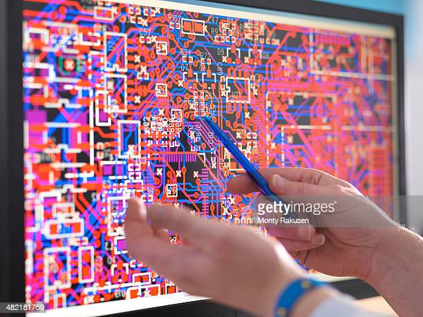 Engineer points to computer screen with electronic circuitry designs for automotive use