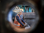 Engineer portrait in factory viewed through hole in steel