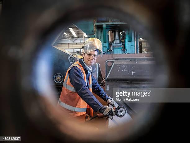 Engineer portrait in factory viewed through hole in steel