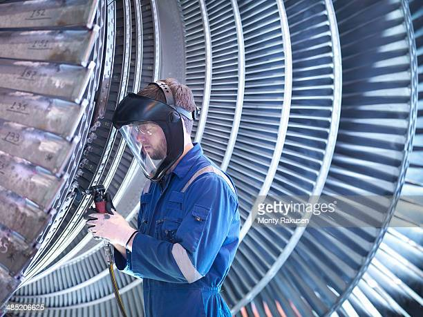 Engineer repairing steam turbine blade with grinder in workshop