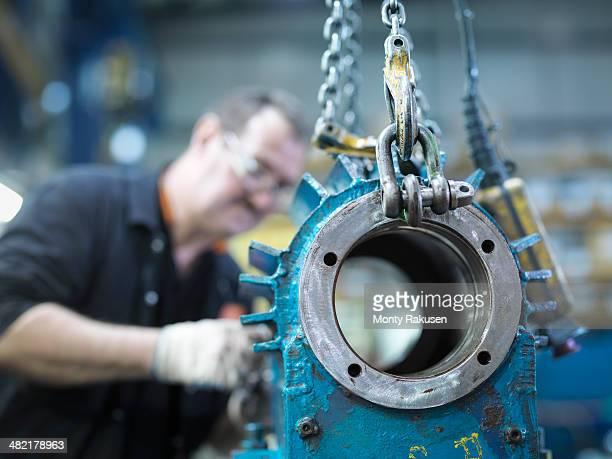 Engineer repairs industrial gearbox in engineering factory