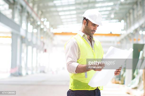 Engineer reviewing plans for construction site.