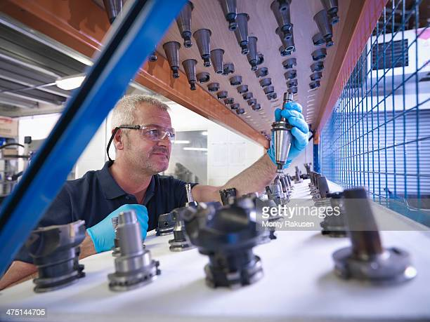 Engineer selecting lathe cutting tools in factory