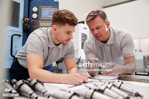 Engineer Showing Apprentice How To Measure CAD Drawings : Stock Photo