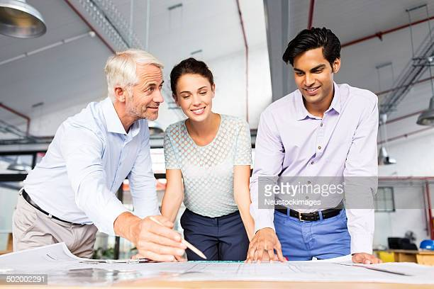 Engineer Showing Blueprint To Colleagues At Office Desk