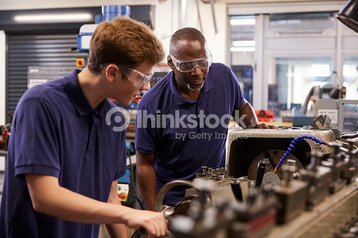 Engineer Showing Teenage Apprentice How To Use Lathe : Stock Photo