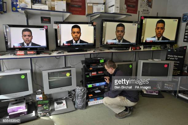 TV engineer Simon Bampfylde in Springer Vision TV shop in Keynsham near Bristol while Labour MP Shahid Malik appears on TV screens