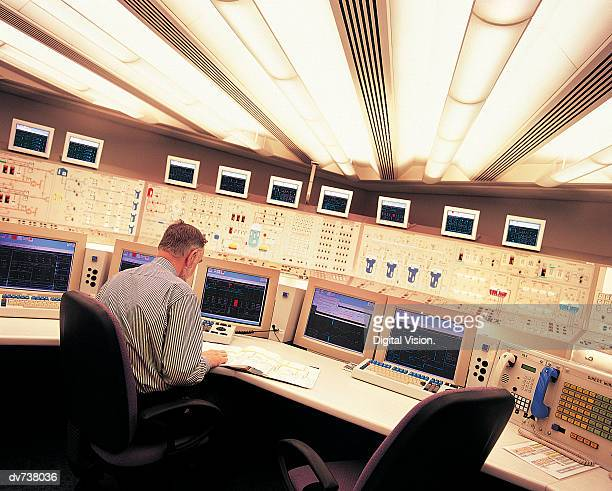 Engineer sitting at control panel of nuclear power station