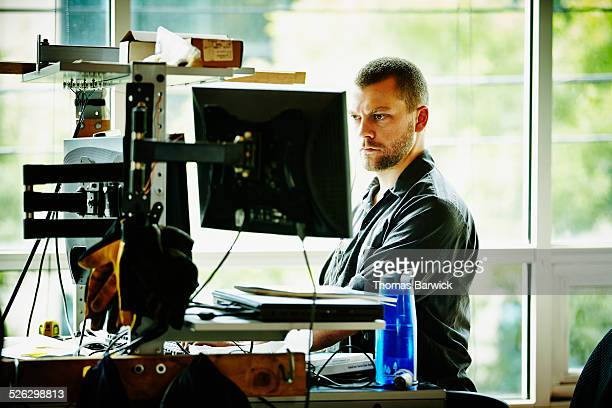 Engineer standing at desk designing project