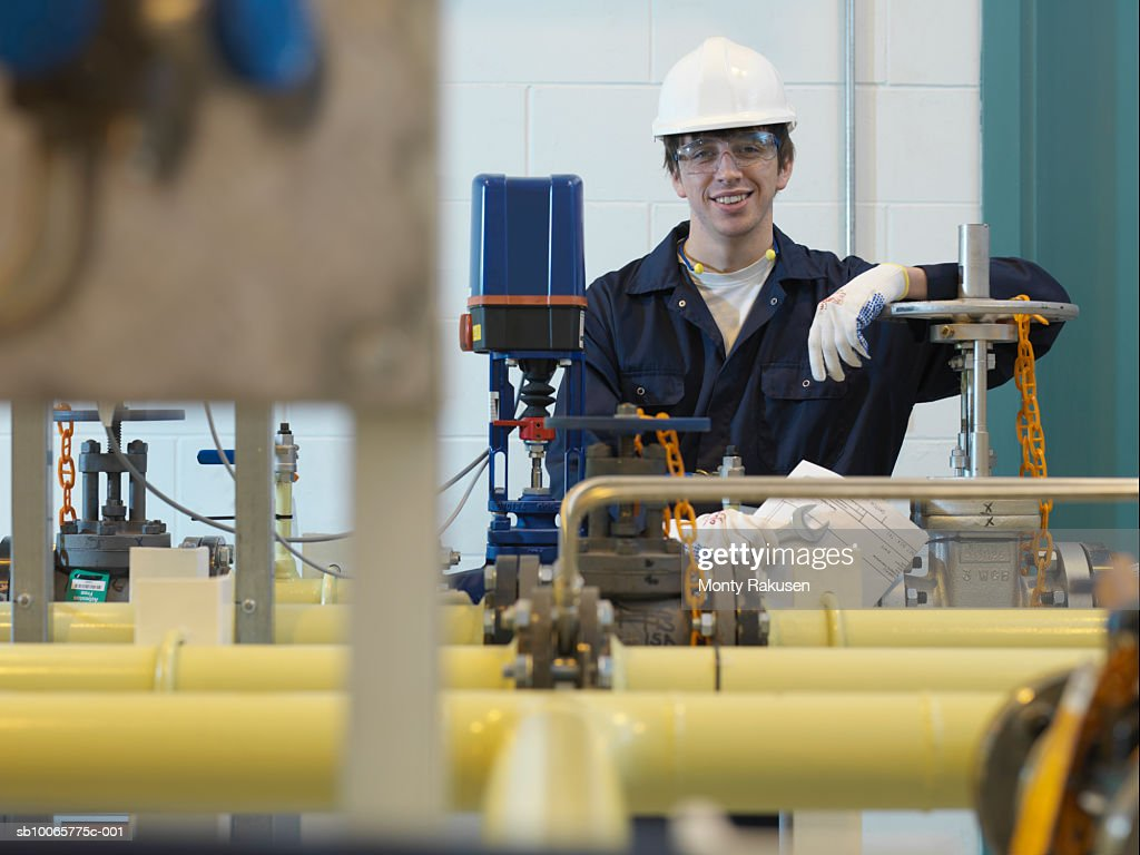 Engineer standing behind machinery, portrait : Stock Photo