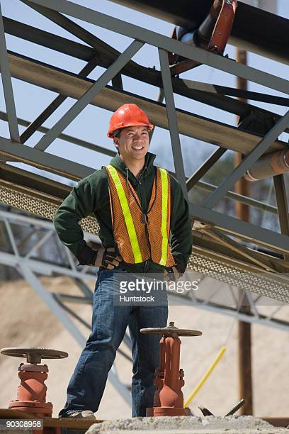 Engineer standing near control valves and smiling