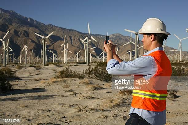 Engineer taking photo of wind turbines
