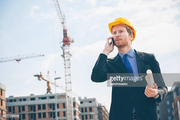 Ingénieur parlant sur le téléphone intelligent et tenant des imprimés bleu