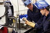Engineer Teaching Apprentice To Use TIG Welding Machine At Work