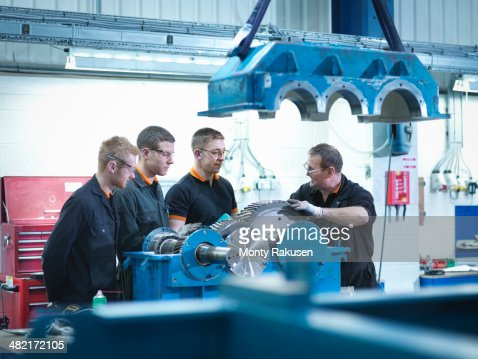 Engineer teaching apprentices in engineering factory