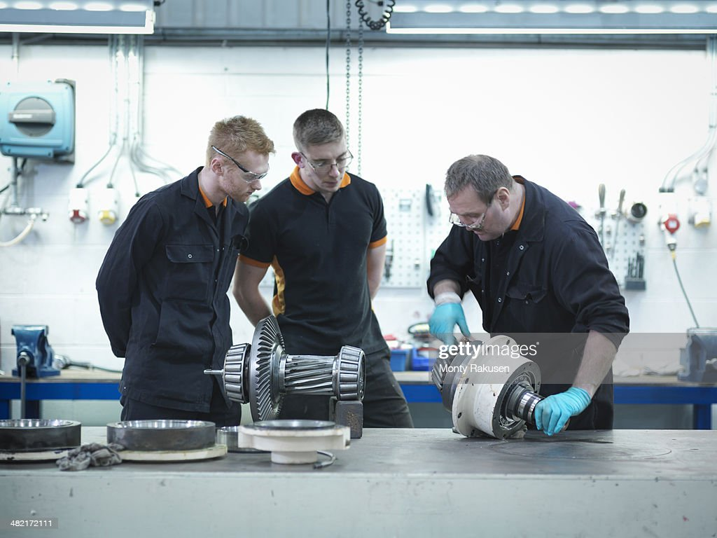 Engineer teaching apprentices in engineering factory : Stock Photo