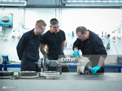 Engineer teaching apprentices in engineering factory : Stock Photo