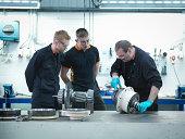Engineer teaching apprentices in engineering factory